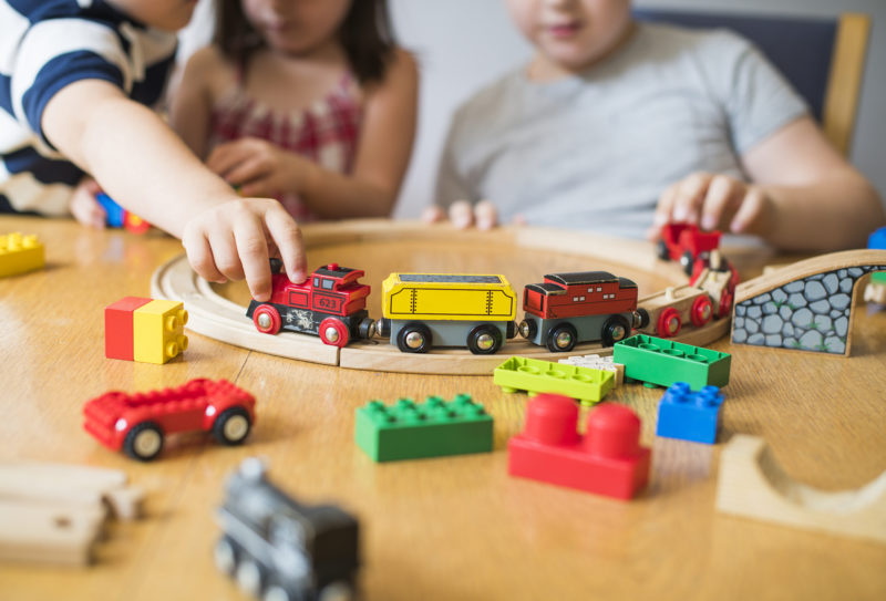Siblings playing with blocks, trains and cars